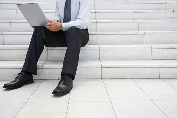 Businessman using laptop on steps outdoors low section